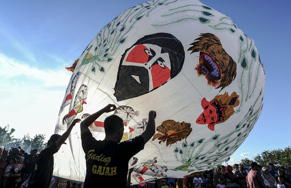 Participants prepare to fill their balloon with hot air before releasing it during the Java Balloon Festival in Nongkodono village, East Java, on Wednesday. (Antara Photo/Harviyan Perdana Putra)