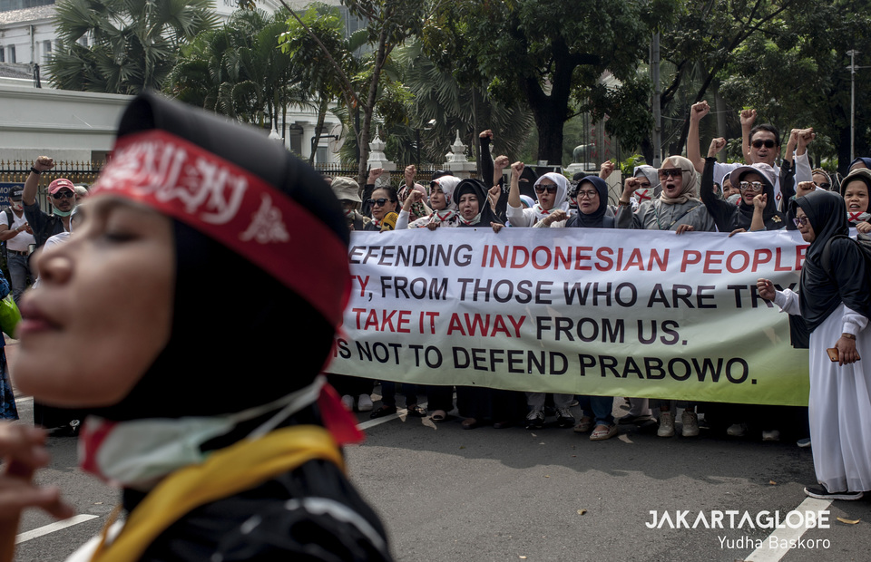 A woman wearing make up before join a group photo during protest in Constitutional Court area, Central Jakarta on Friday (16/04) (JG Photo/Yudha Baskoro)