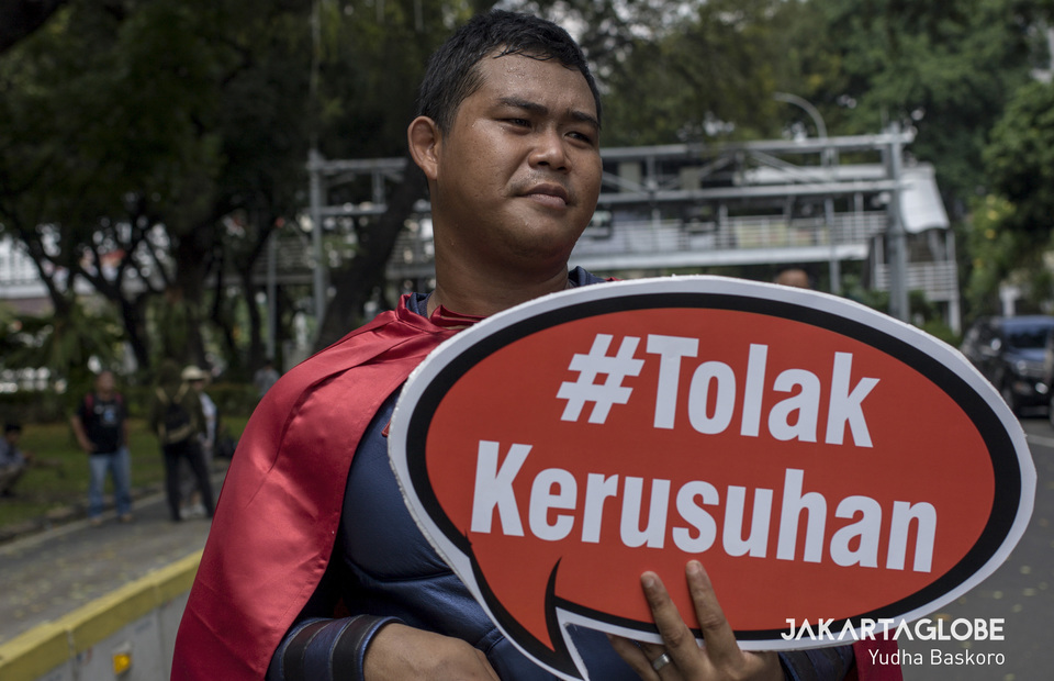Superman walks from Arjuna Wiwaha horse statue to near Constitutional Court and brings placard reads Tolak Kerusuhan on Tuesday (18/06) (JG Photo/Yudha Baskoro)