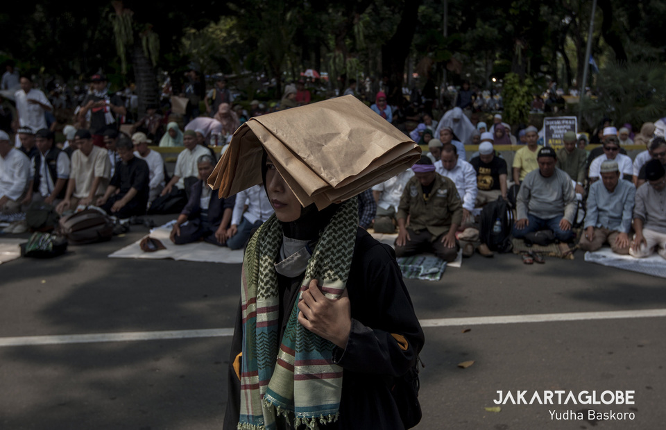 Woman stands in front of people praying during protest in Constitutional Court, Central Jakarta on Thursday (27/06) (JG Photo/Yudha Baskoro)