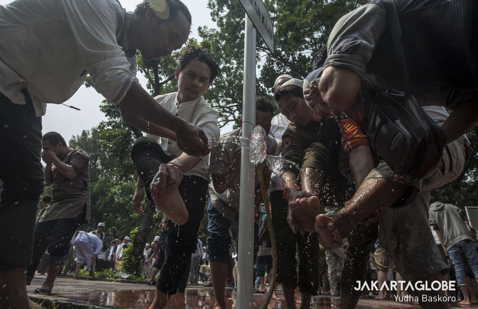 Protesters take ablution water during dzuhur prayer in front of Constitutional Court on Thursday (27/06)(JG Photo/Yudha Baskoro)