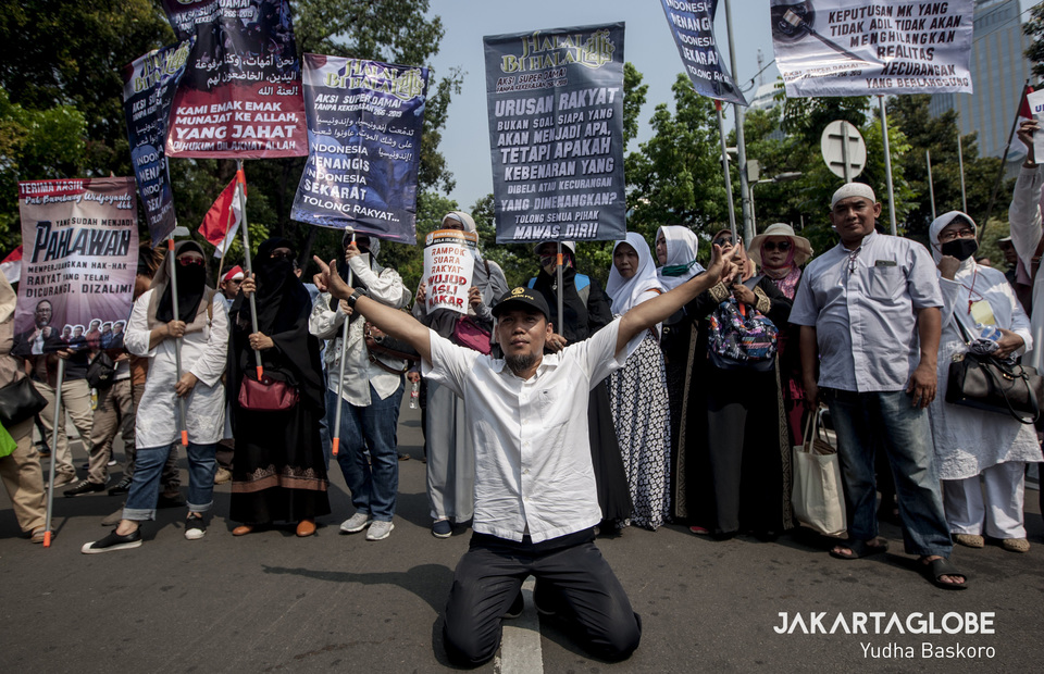 Demonstrators wearing islamic attire and bring placard reads that the incumbent and his running mate alleged to fraud during the general election. (JG Photo/Yudha Baskoro)