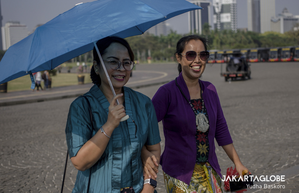 The founder of Kebaya Tuesday Rahmi Hidayati (51) wearing her purple kebaya walks around the National Monument with her friend to spread the campaign on Tuesday (02/07) (JG Photo/Yudha Baskoro)