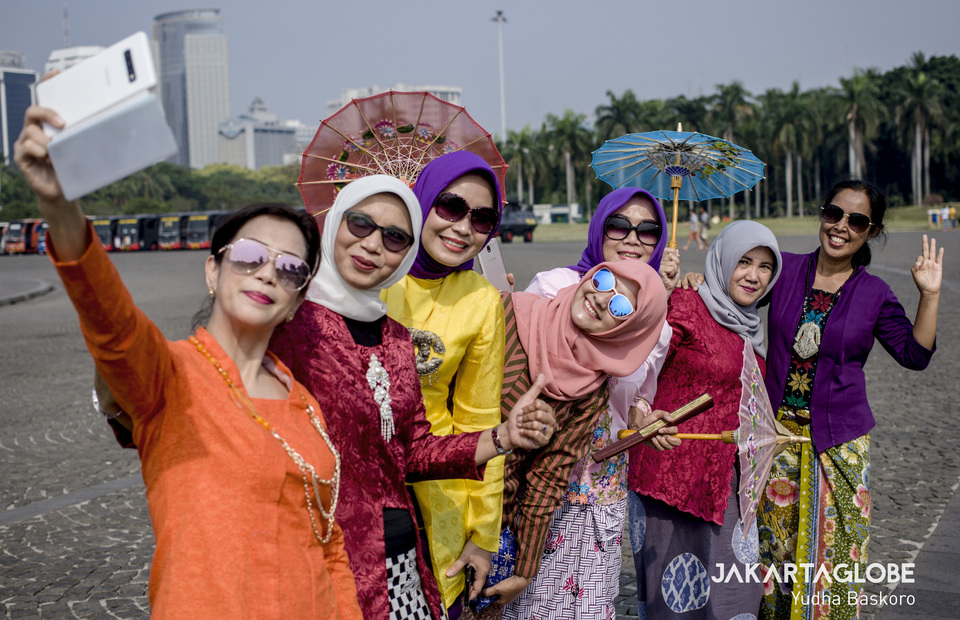 Kebaya Tuesday participants take selfie photos in front of National Monument in Central Jakarta on Tuesday (02/07) They spread the campaign through social media (JG Photo/Yudha Baskoro)