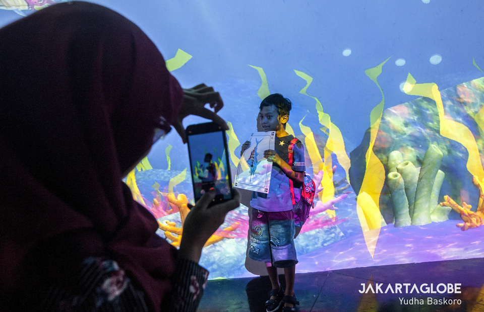 Visitor of TeamLab Future Park take a self portrait with his drawing in front of Sketch Aquarium art instalation on Wednesday (03/07) (JG Photo/Yudha Baskoro)