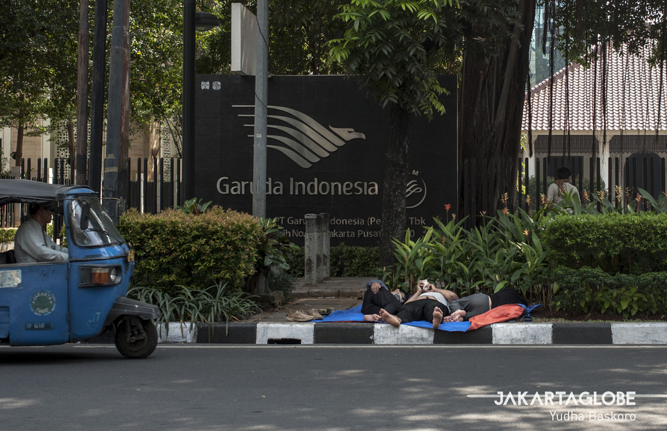 Bajaj passes by sleeping refugees in front of Garuda Indonesia office building at Jalan Kebon Sirih, Central Jakarta on Monday (08/07) (JG Photo/Yudha Baskoro)