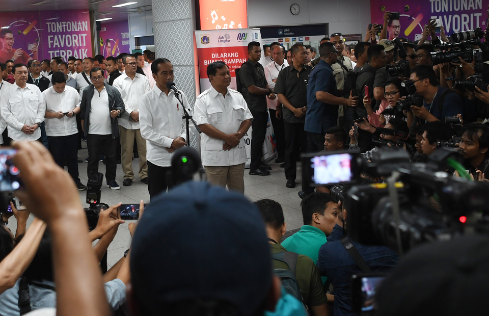 President Joko 'Jokowi' Widodo and his former challenger Prabowo Subianto greet the press at MRT Senayan Station on Saturday (13/07) (Antara Photo/Wahyu Putro A)