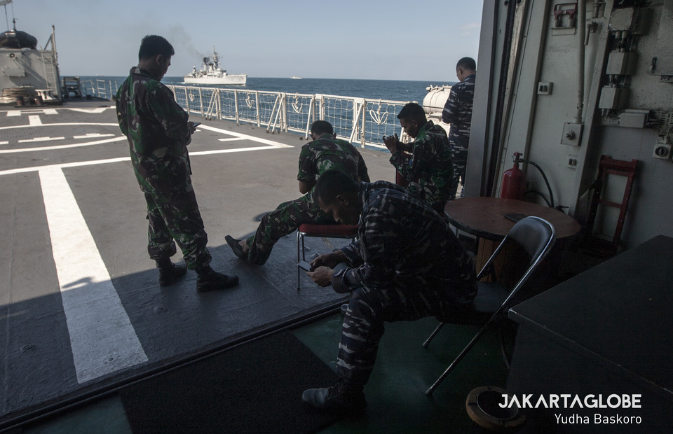 Indonesian Navy personnels sit on the stern of the ship as they wait for signal comes to their mobile phone after finishing their training on Friday (12/07) (JG Photo/Yudha Baskoro)