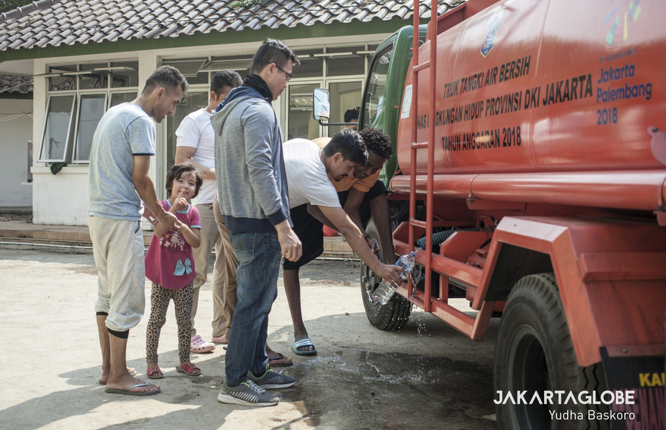 Refugee scollect clean water with bottles when receiving clean water supply from the Jakarta Environmental Service (JG Photo/Yudha Baskoro)