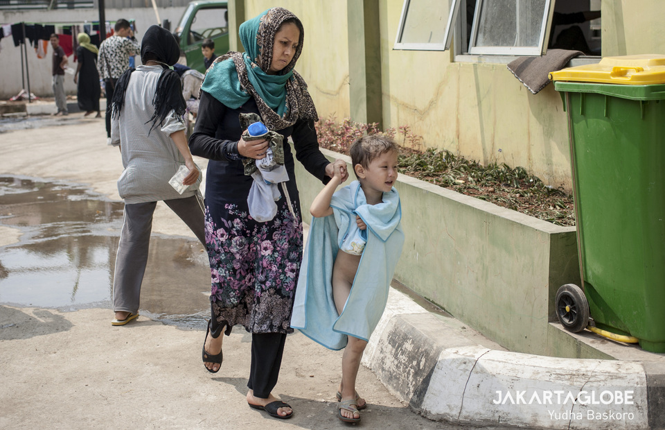Child refugee walk with his mother after take a shower on a daytime to save clean water supplies at relocation area in Kalideres, West Jakarta on Monday (15/07) (JG Photo/Yudha Baskoro)