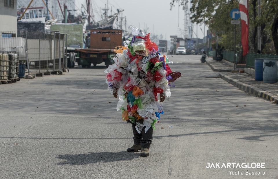 An activist walks alongside the Sunda Kelapa Port as a symbol of human who feels hot and difficult to move because he is covered by piles of plastic waste (JG Photo/Yudha Baskoro)
