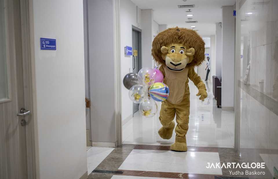 An entertainer wearing lion costume visits child in-patient rooms during National Children