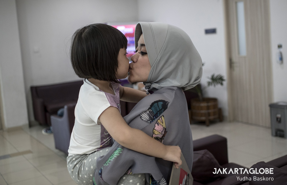 A mother kisses her daughter during National Children