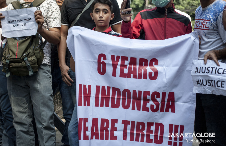A child refugee participates in protest and brings placard that said '6 years in Indonesia We are tired' (JG Photo/Yudha Baskoro)