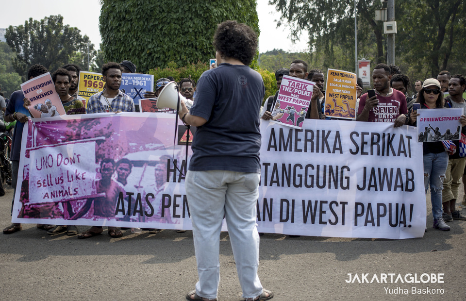 Protesters carry a banner with a demand that the United States take full responsibility for the massacres that occurred in West Papua in the 1960s. (JG Photo/Yudha Baskoro)