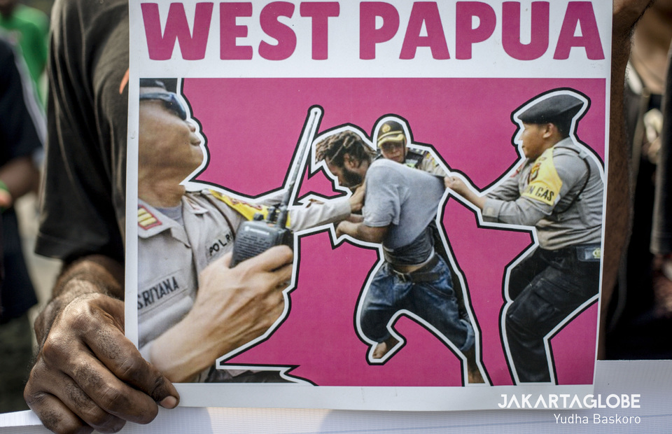 A placard shows alleged police brutality against a Papuan activist. (JG Photo/Yudha Baskoro
