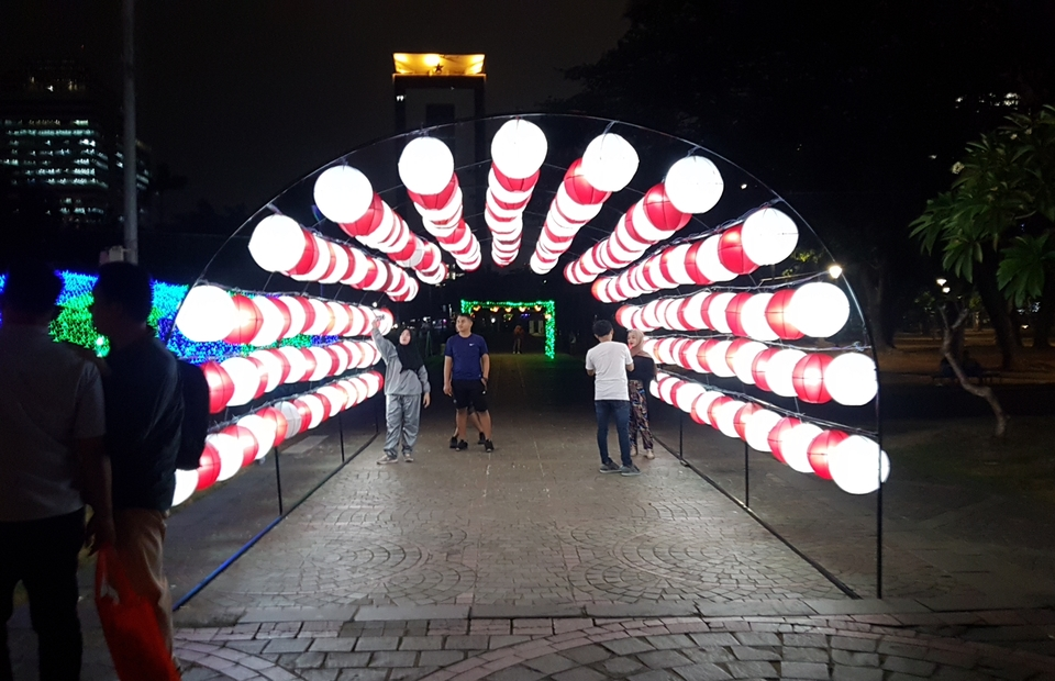 People taking photos at lampoon gate at Festival of Lights, at National Monument, Jakarta. (JG Photo/Nur Yasmin)