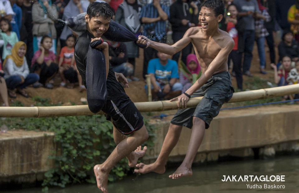 Residents line the banks of the Kalimalang River in East Jakarta to watch a pillow fight. (JG Photo/Yudha Baskoro)