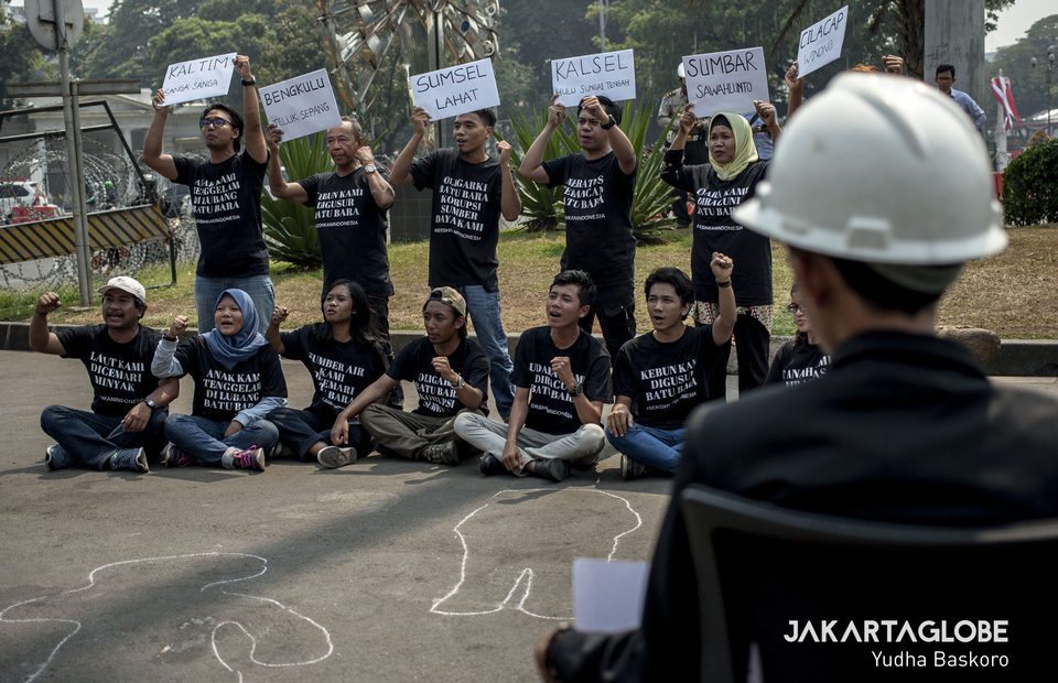 Activists carried placards that read the names of regions in Indonesia affected by coal mines during protest in front of the State Palace, Central Jakarta on Monday (19/08). (JG Photo / Yudha Baskoro)