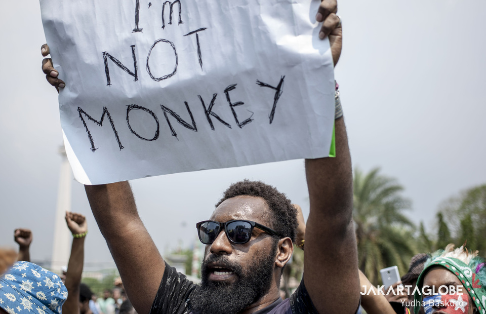 A man carries a placard that said Im not a monkey during protest in front of State Palace, Central Jakarta on Thursday (22/08). (JG Photo/Yudha Baskoro)