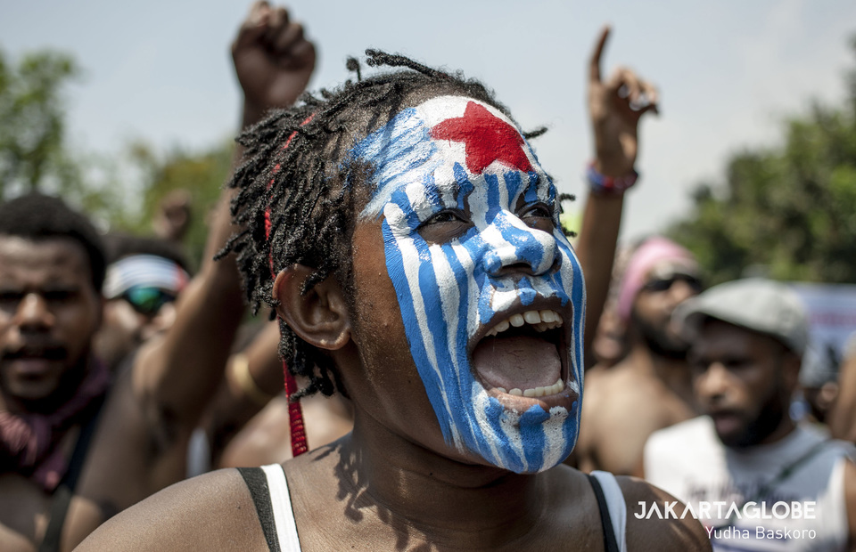 A woman paints her face with West Papua flag during protest in front of State Palace, Central Jakarta on Thursday (22/08). (JG Photo/Yudha Baskoro)