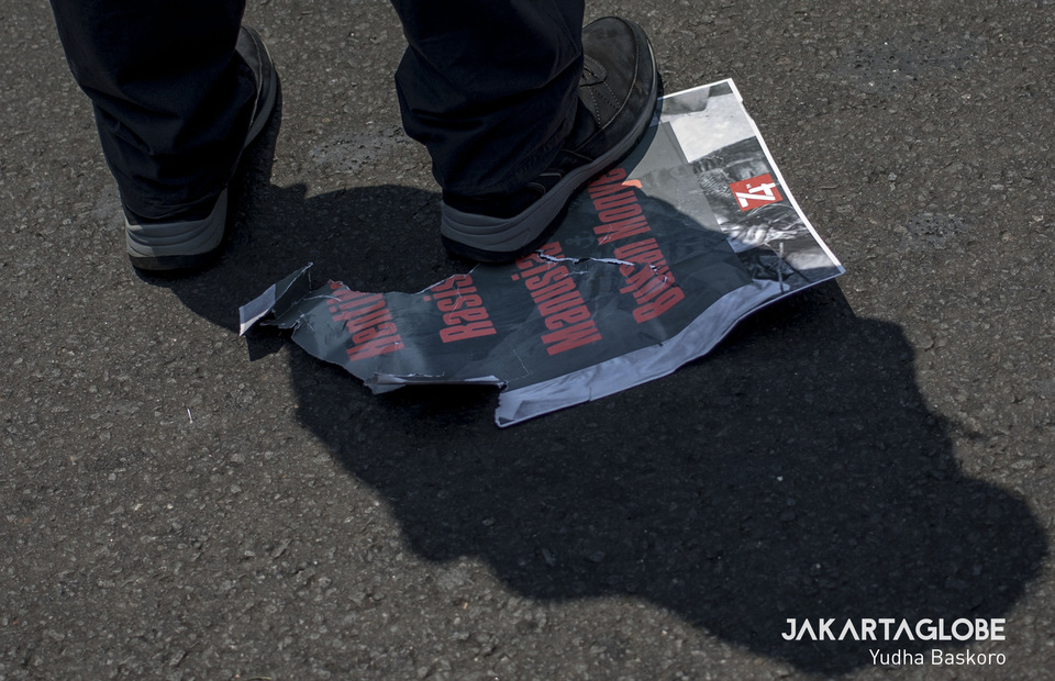 A man steps on a poster that written stop racism, we are not monkey. (JG Photo/Yudha Baskoro)
