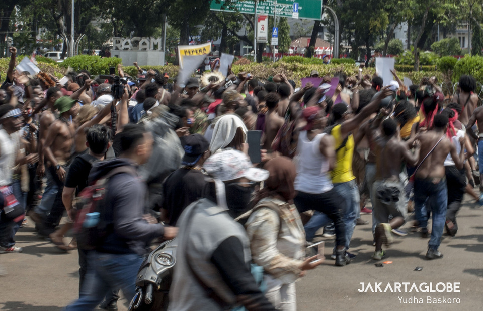 Protesters form a circle and sing songs in the Papuan language during protest in front of State Palace, Central Jakarta on Thursday (22/08). (JG Photo/Yudha Baskoro)