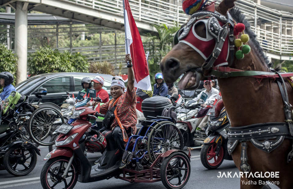 A man waves the national flag while riding on a modified motorcycle during the march along Jalan M.H. Thamrin in Central Jakarta. (JG Photo/Yudha Baskoro)