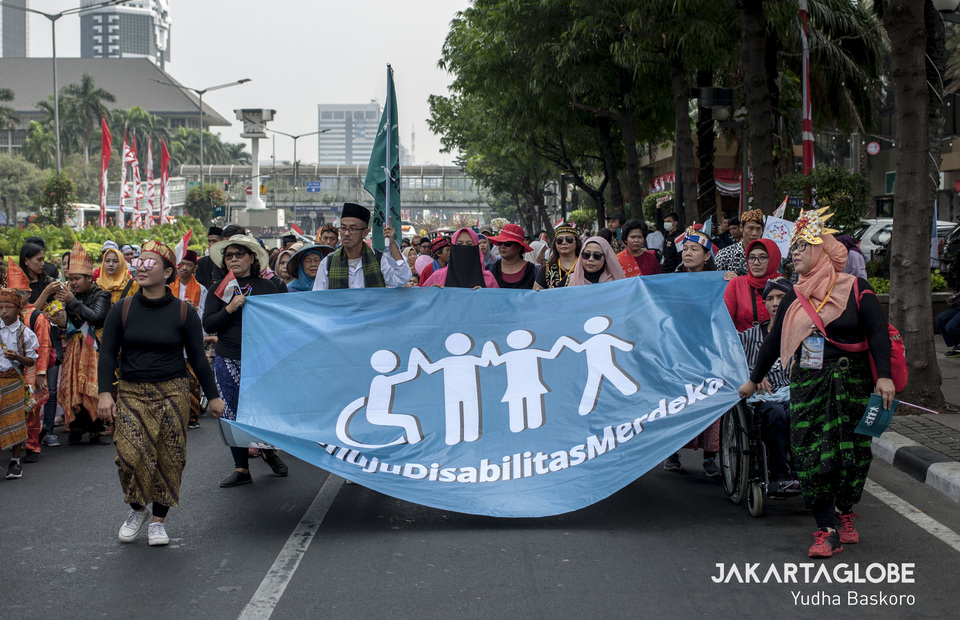 Participants carry a banner promoting greater independence for people with disabilities. (JG Photo/Yudha Baskoro)