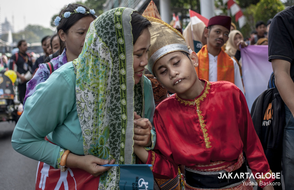 A woman assists her child while participating in the march. (JG Photo/Yudha Baskoro)