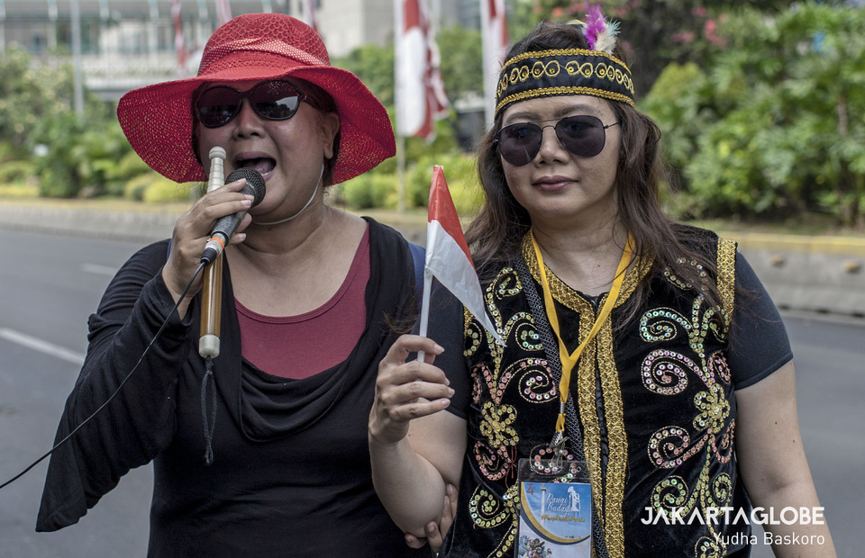 A blind woman addresses the crowd on discrimination against people with disabilities during the gathering at the Arjuna Wiwaha Statue. (JG Photo/Yudha Baskoro)