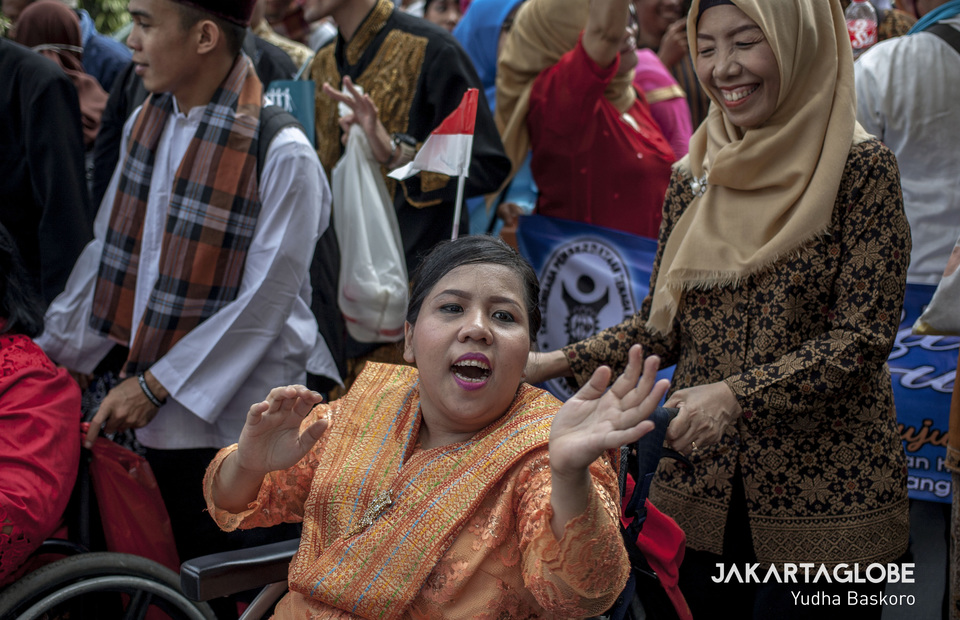 A woman dances in her wheelchair to the sound of a traditional Bataknese song. (JG Photo/Yudha Baskoro)