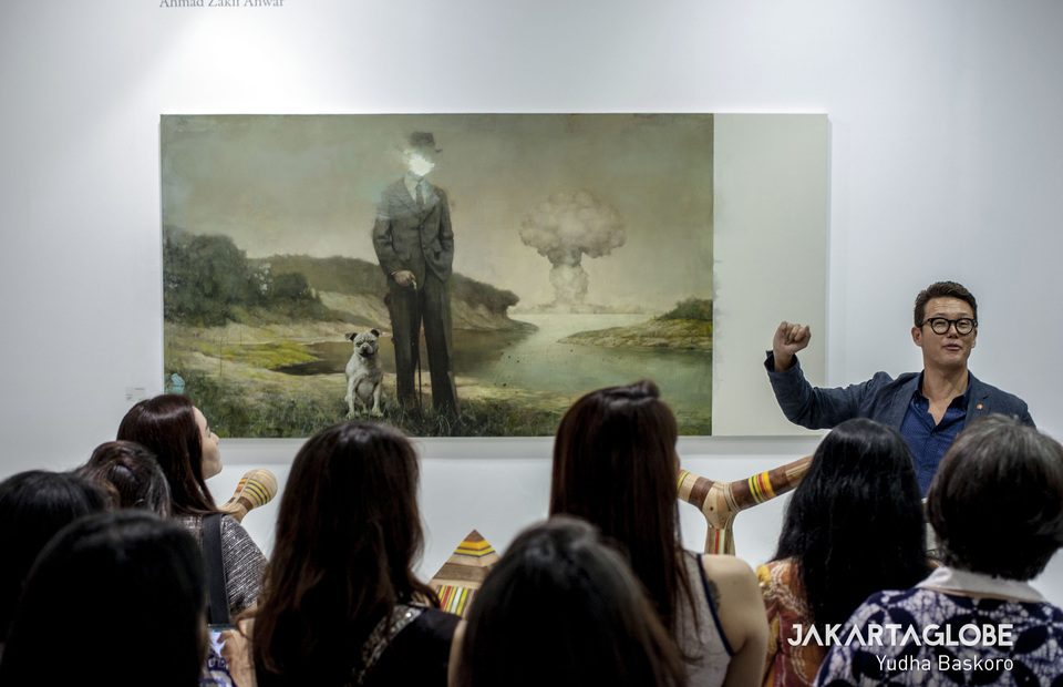 A curator discusses a painting by well-known Malaysian artist Ahmad Zakii Anwar during the opening day of Art Jakarta 2019 on Friday. (JG Photo/Yudha Baskoro)
