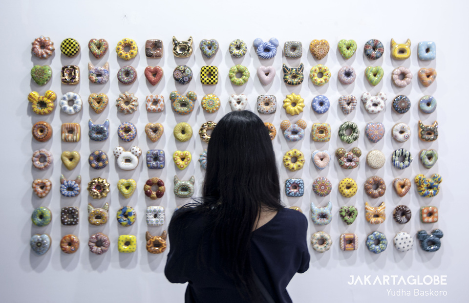 A visitor takes a photo of 'Donut Rush' by South Korean ceramicist Jae Yong Kim. (JG Photo/Yudha Baskoro)