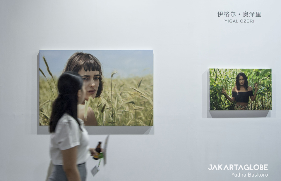 A visitor passes a hyper-realistic painting by Israeli-born artist Yigal Ozeri. (JG Photo/Yudha Baskoro)