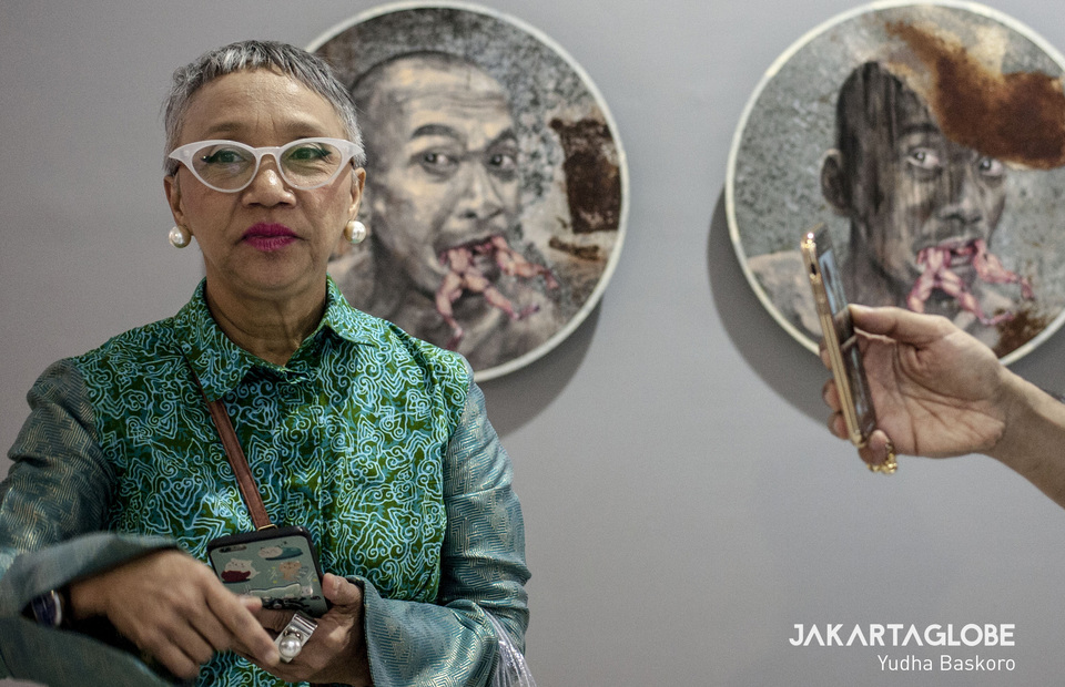 A visitor stands in front of works belonging to ROH Projects. (JG Photo/Yudha Baskoro)
