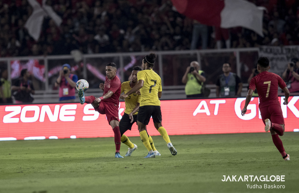 Indonesia's Alberto 'Beto' Gonçalves controls the ball while outnumbered by Malaysian opponents. (JG Photo/Yudha Baskoro)