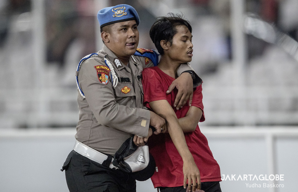 A policeman escorts the instigator of a clash between Indonesian and Malaysian supporters off the field. (JG Photo/Yudha Baskoro)