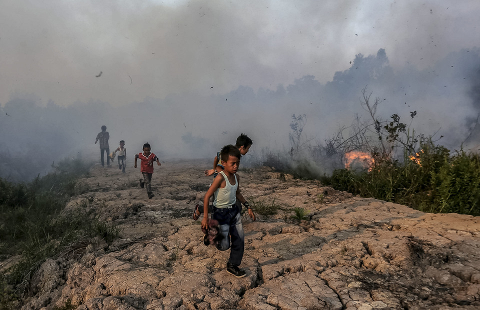 Children ran to avoid land fires in Kayu Arehh Village, Kertapati Palembang, South Sumatra on Sunday (18/08). (Antara Photo/Mushaful Imam)