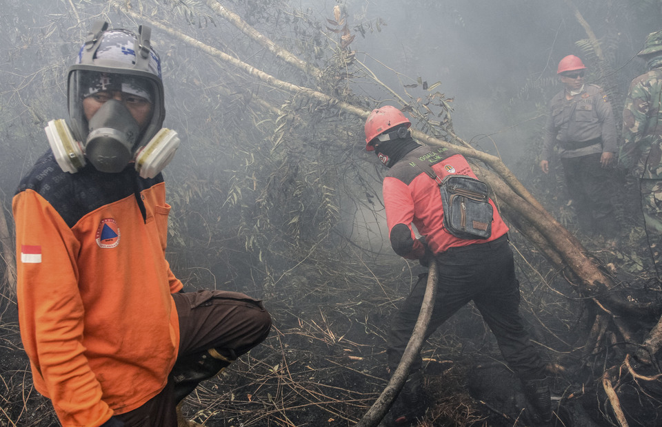 Firefighters put out a forest fires in Rimbo Panjang Village, Kampar Regency, Riau on Monday (16/09). (Antara Photo/ Rony Muharrman)