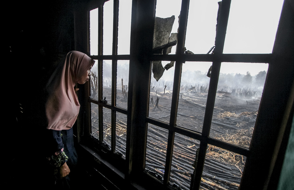Residents saw peatland fires from behind the window at her home in Pengayuan village, Banjarbaru, South Kalimantan on Saturday (14/09). (Antara Photo/Bayu Pratama S)