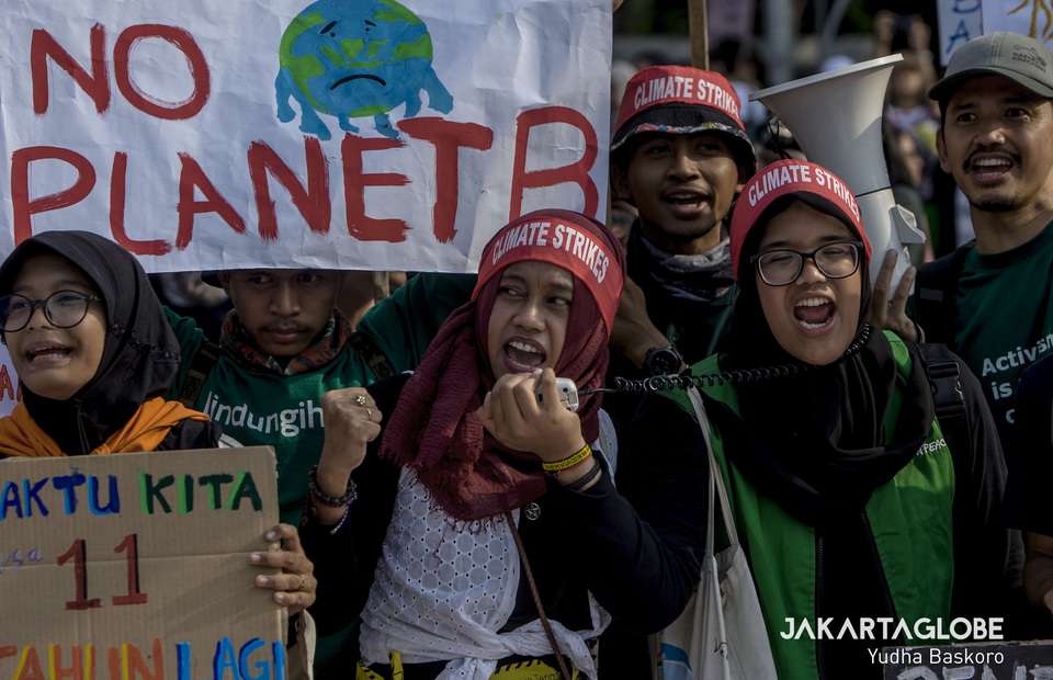 A woman leads the protesters to critic the goverment during global climate change protest in front of State Palace, Central Jakarta on Friday (20/09). (JG Photo/Yudha Baskoro)
