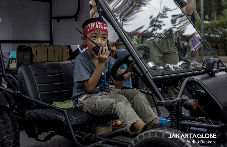 A young boy talks with walkie talkie inside a solar-powered car as he leads the climate change protesters to go through U.S Embassy in Central Jakarta on Friday (20/09). (JG Photo/Yudha Baskoro)