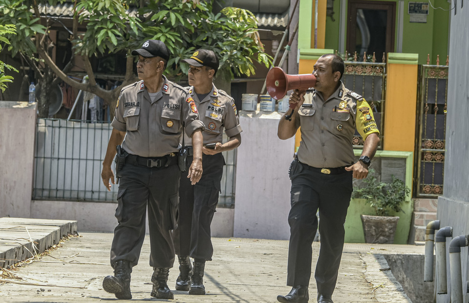 Police officers order warn residents to stay clear of the terror suspect's home in Semper Barat village, North Jakarta. (Antara Photo/Muhammad Adimaja)