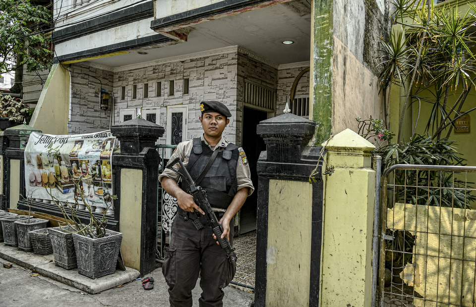 A policeman stands guard in front of the terror suspect's home. (Antara Photo/Muhammad Adimaja)