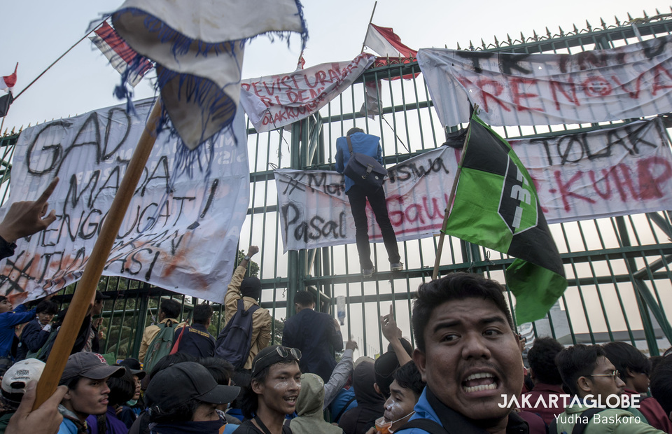 A protester tries to scale the fence around the legislative complex. (JG Photo/Yudha Baskoro)