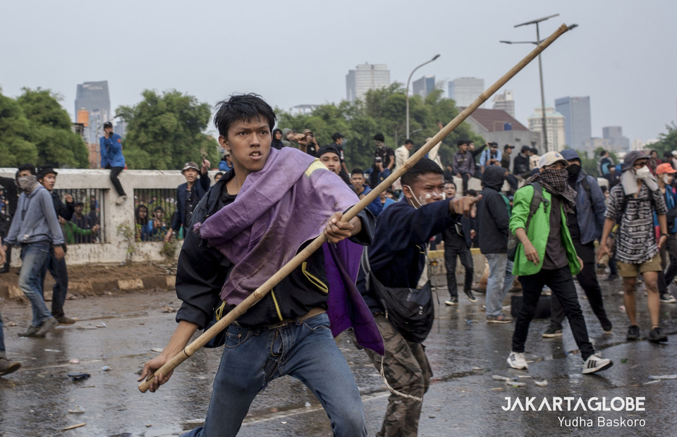A protester carries a bamboo stick during the clash. (JG Photo/Yudha Baskoro)