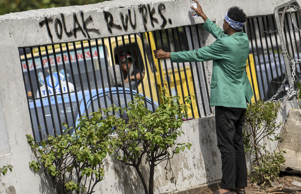 Student makes a graffiti that reads reject the sexual violence eradiction bill during protest in front of DPR/MPR Buidling in Senayan, Central Jakarta on Monday (30/09). (Antara Photo/Aditya Pradana Putra)