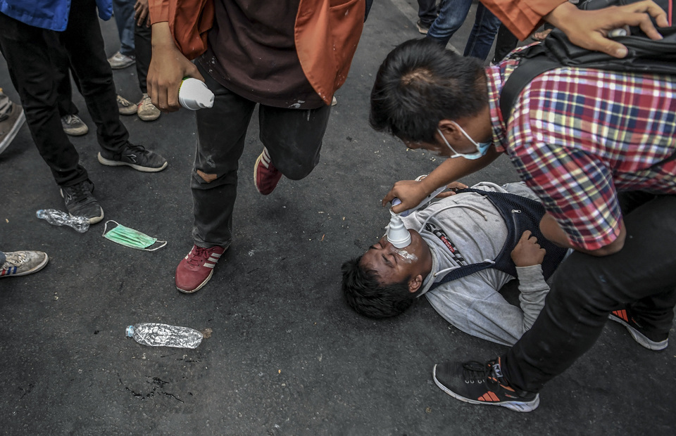 Protester receive oxygen assist after hit by tear gas during protest near parliament complex building in Senayan, Central Jakarta on Monday (30/09). (Antara Photo/Hafidz Mubarak A)