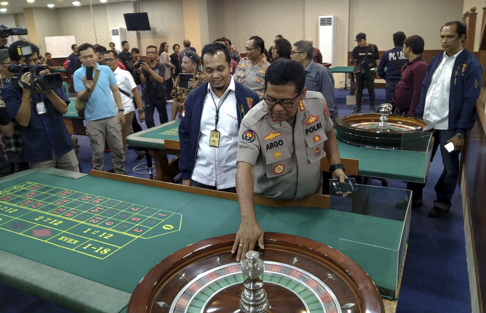 The police officers inspect a roulette table inside the covert casino. (SP Photo/Carlos Roy Fajarta Barus)